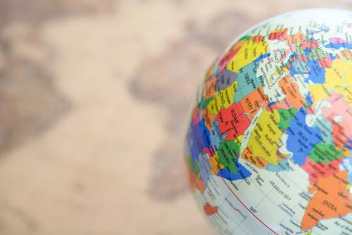 A colorful globe in the foreground shown over a blurred map in the background.