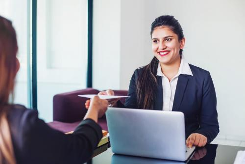 A smiling medium-light skin-toned woman in business attire sits in front of a computer and accepts a letter from another medium skin-toned woman.
