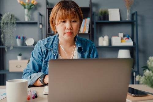A medium-skinned woman works at a laptop in her apartment.