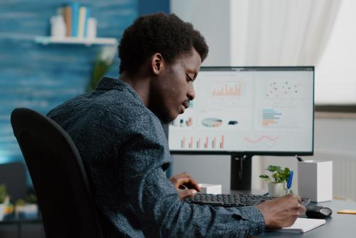 A dark-skinned man sits at a desk taking notes in a notebook. His computer monitor displays a dashboard.