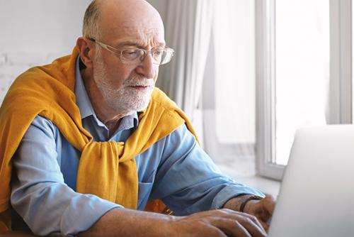 Older light-skinned man with glasses working on a laptop.