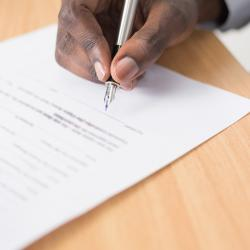 A hand holds a pen, getting ready to sign the bottom of a document.